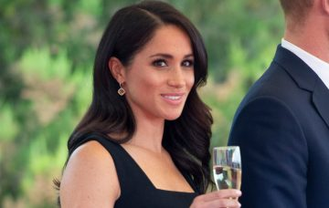 Meghan smiles with champagne glass