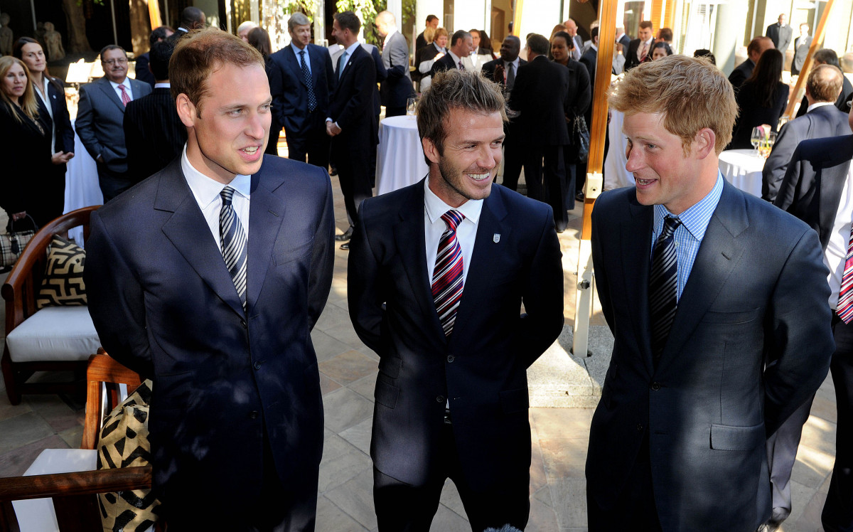 Prince William speaks to David Beckham (C) and Prince Harry (R) at an FA reception at the Saxon Hotel on June 19, 2010