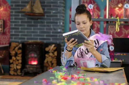 Cleo receives a book in Hollyoaks