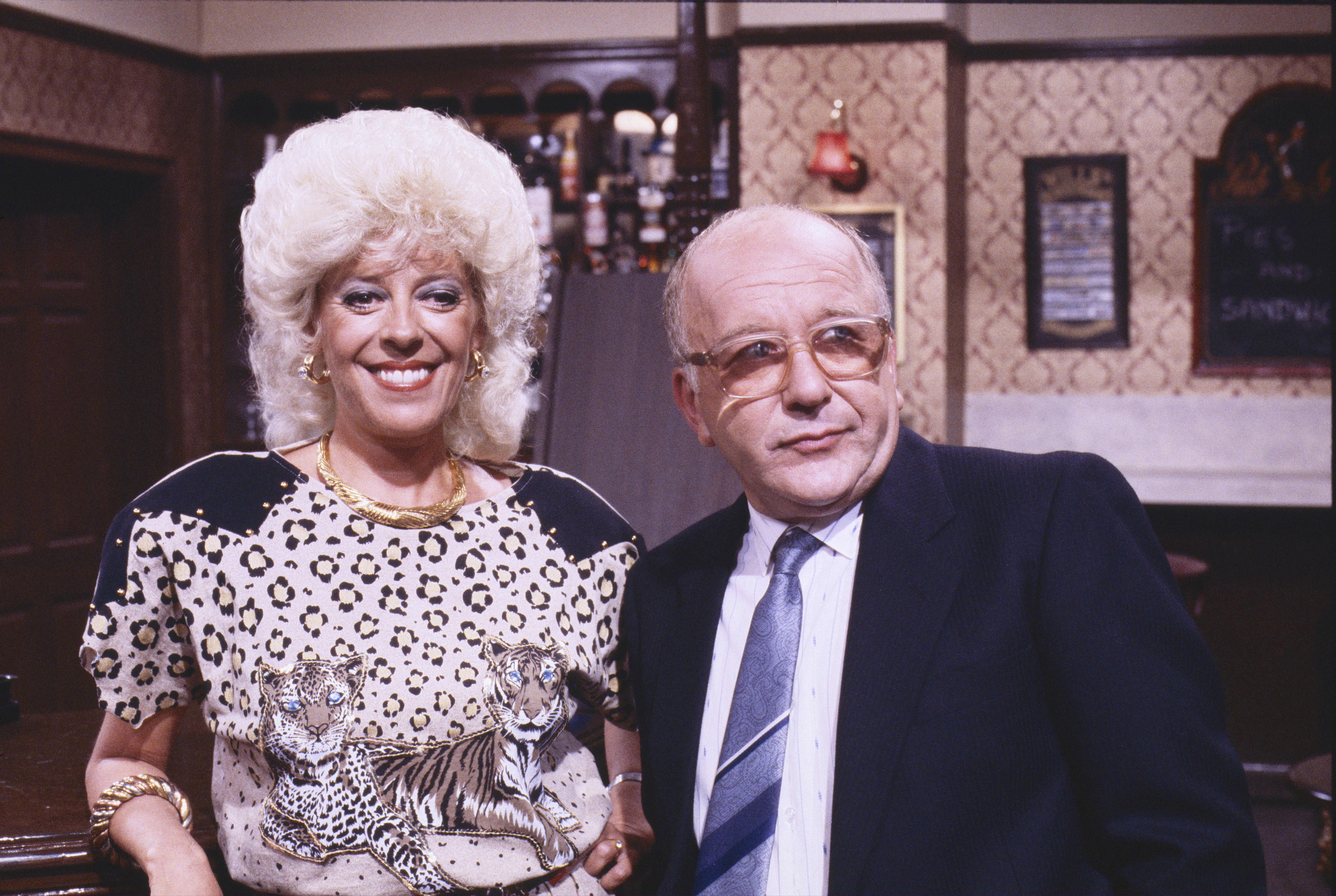 """Editorial use only Mandatory Credit: Photo by ITV/REX/Shutterstock (8811957cr) Julie Goodyear (as Bet Gilroy) and Roy Barraclough (as Alec Gilroy) """"Coronation Street"""" TV series - 1987 Coronation Street is a long running Television soap opera set in the fictional North of England town of Weatherfield. Created by Tony Warren. First broadcast on December 9th, 1960. Produced by ITV Granada."""