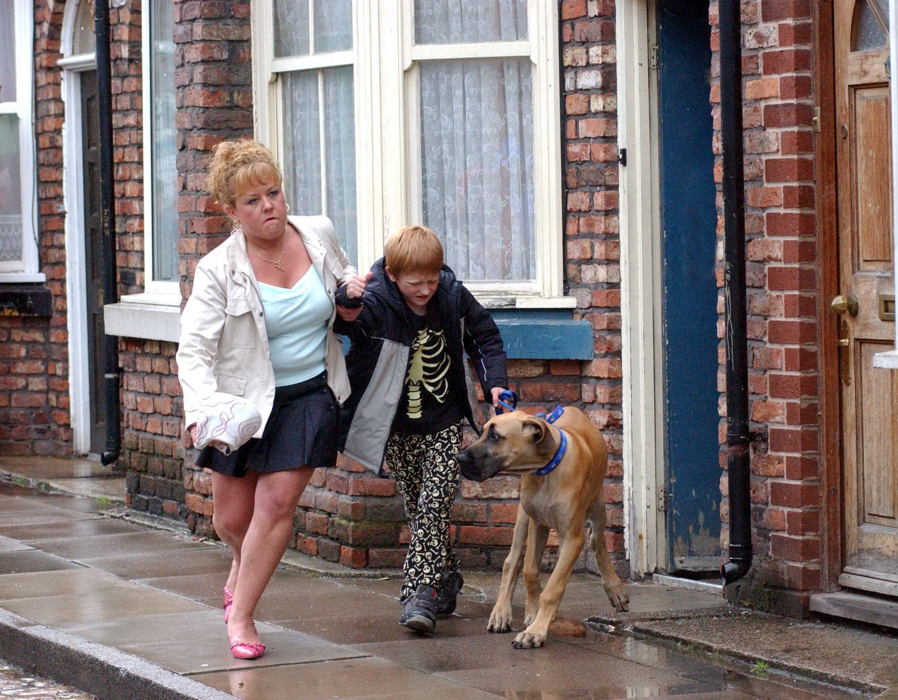 Editorial use only. Exclusive - Premium Rates Apply. Call your Account Manager for pricing. Mandatory Credit: Photo by ITV/REX/Shutterstock (710618lb) 'Coronation Street' TV - 2004 - After Janice's ultimatum Les has no choice but to send Chesney on his way. A furious Cilla grabs him by the hand and drags him down the street with Schmeichel in tow. Cilla Brown [Wendi Peters], Chesney Brown [Sam Aston] and Schmeichel [Great Dane]. ITV ARCHIVE