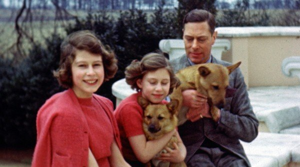 A still image taken from rare archive footage showing Princess Elizabeth, Princess Margaret and their father King George VI with their corgis (HM The Queen)