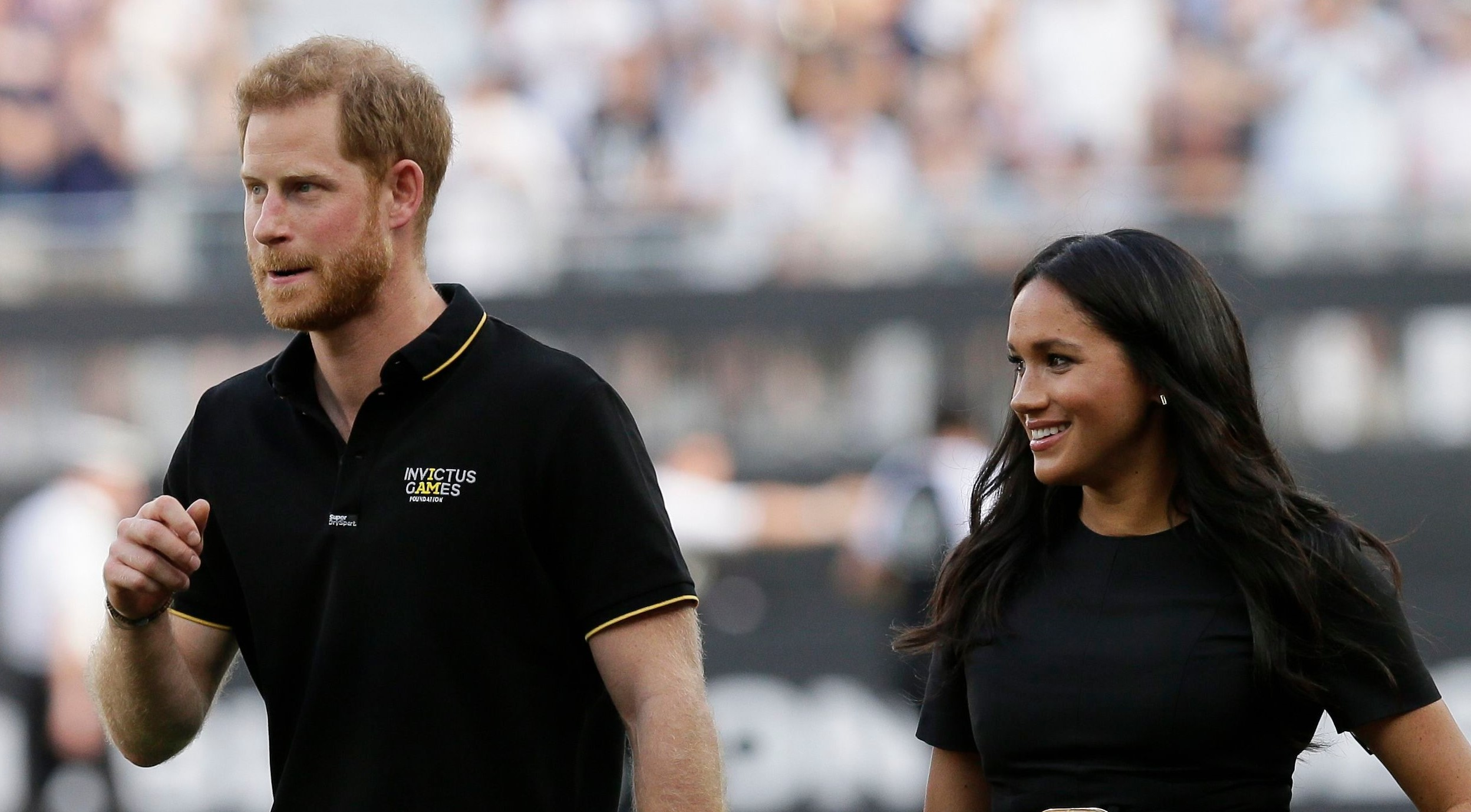 Glowing Meghan enjoys night out with Harry at baseball match