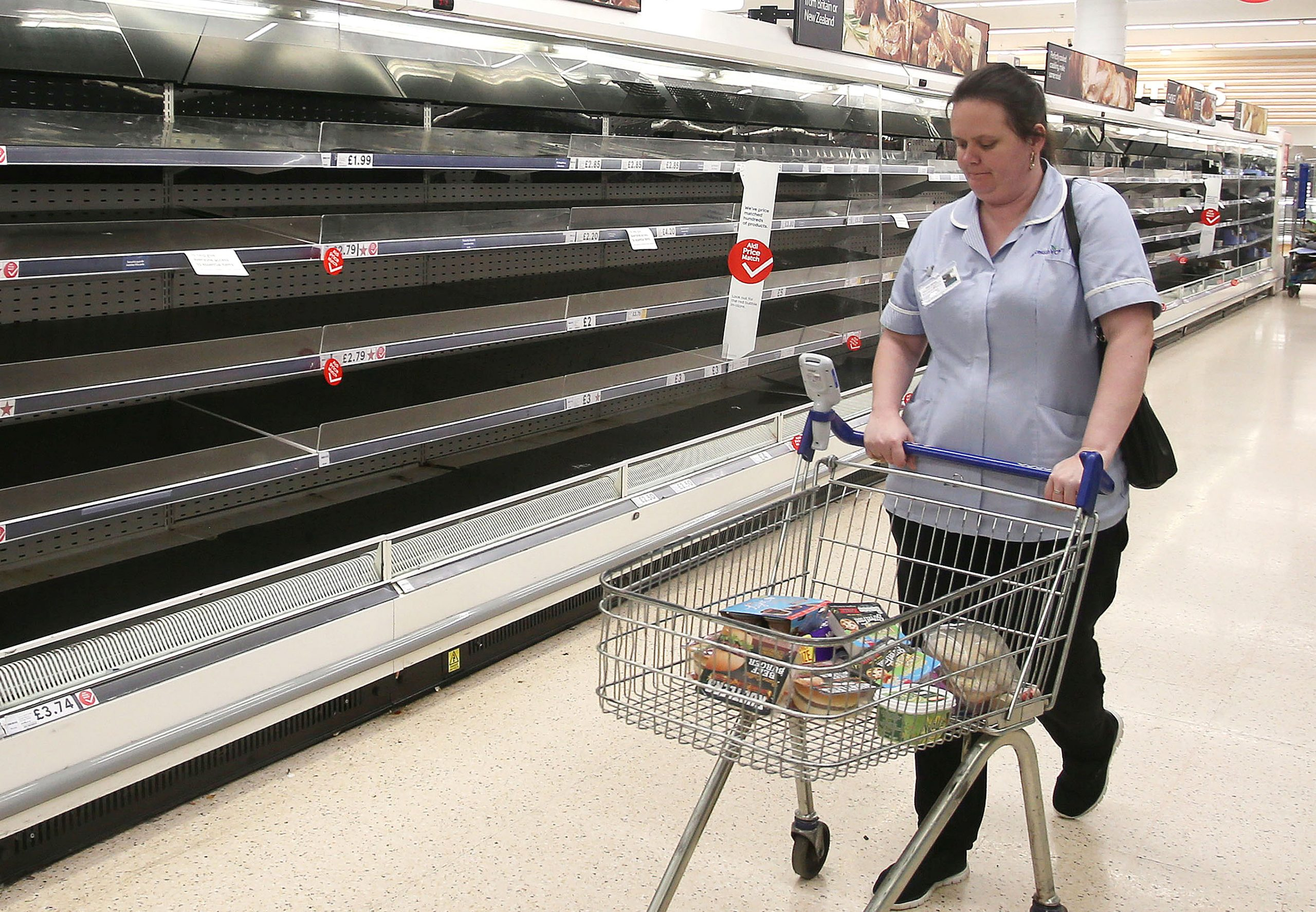A nurse looking at empty shelves at Tesco. Coronavirus: Tesco store introduces one-item limit on essentials such as bread and milk
