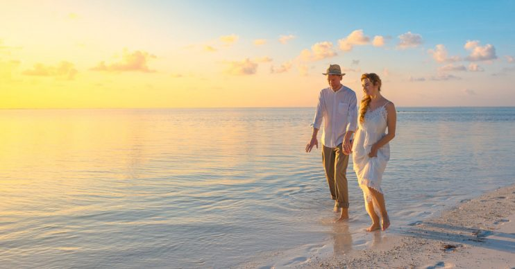 Couple walking on a beach. Coronavirus: UK Foreign Office warns Brits not to travel 'indefinitely'