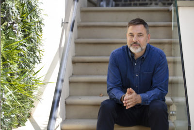 David Walliams sits on steps outside leafy house