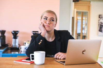 woman sitting at her laptop looking unhappy