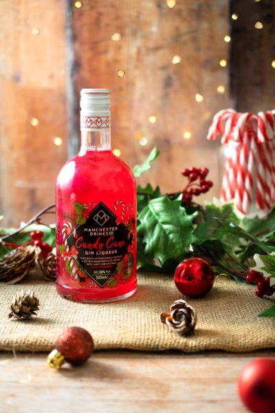 bottle of candy cane gin with pine cones and candy canes around it