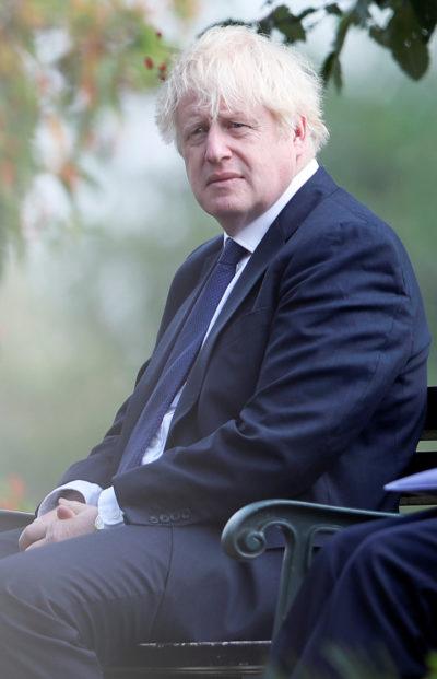 Boris Johnson sitting outside on a bench