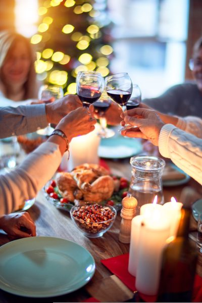People sitting at a Christmas dinner table with wine