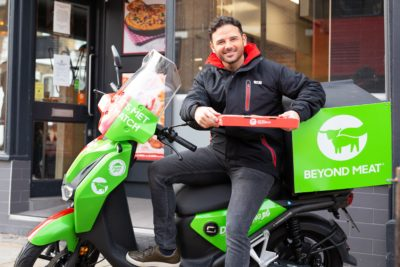 Ryan Thomas on a motorbike delivering pizza