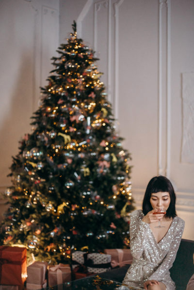 Woman drinking cocktails in front of a Christmas tree