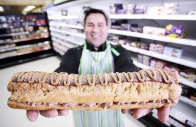 man holding giant chocolate eclair