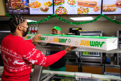 man carrying subway giant pigs in blanket sub