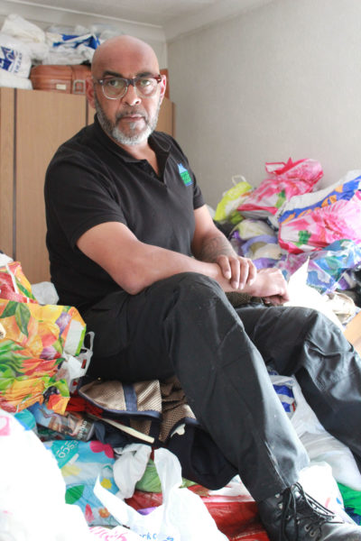 George the cleaner sits on Anne Marie's mountain of hoarded books (Credit: Channel 5)