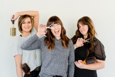 three hairdressers posing with scissors