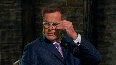 Peter Jones tries out the necklace reading glasses on Dragons' Den (Credit: BBC One)