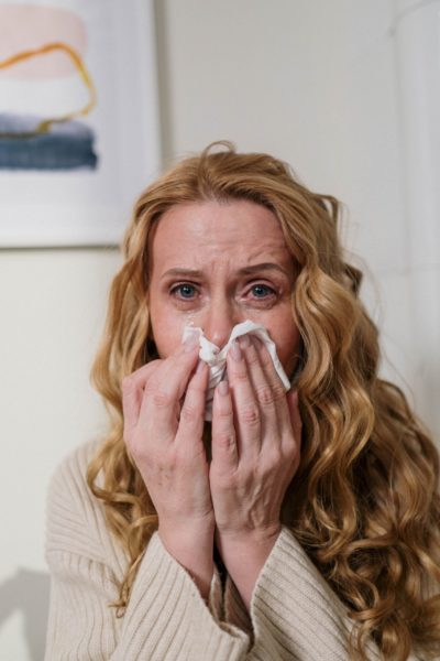 woman with a tissue looking ill