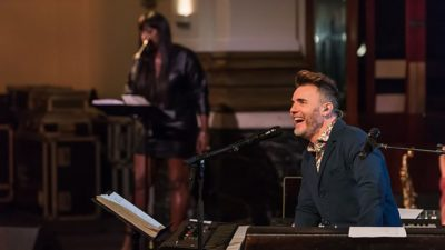 Gary Barlow smiles at the piano on the set of his new tv show