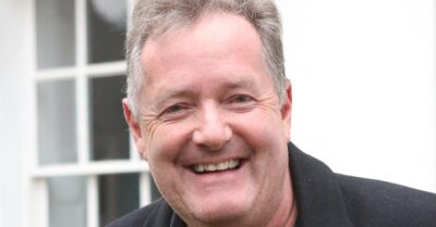 Piers Morgan smiling as he stands outside