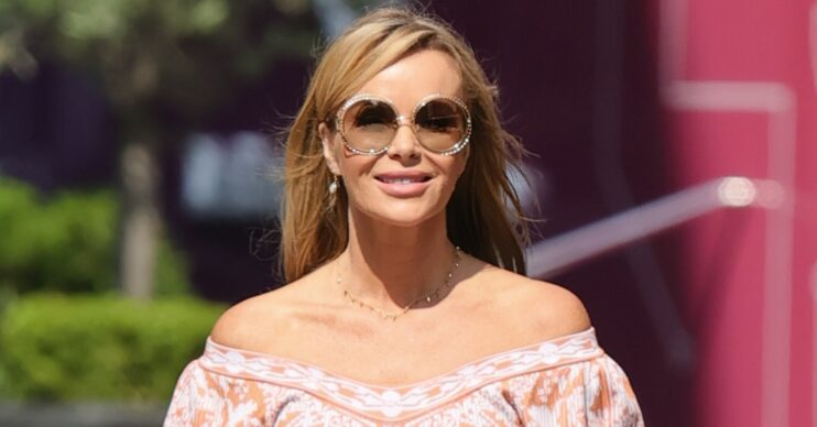 Amanda Holden walking in a summery outfit and sunglasses