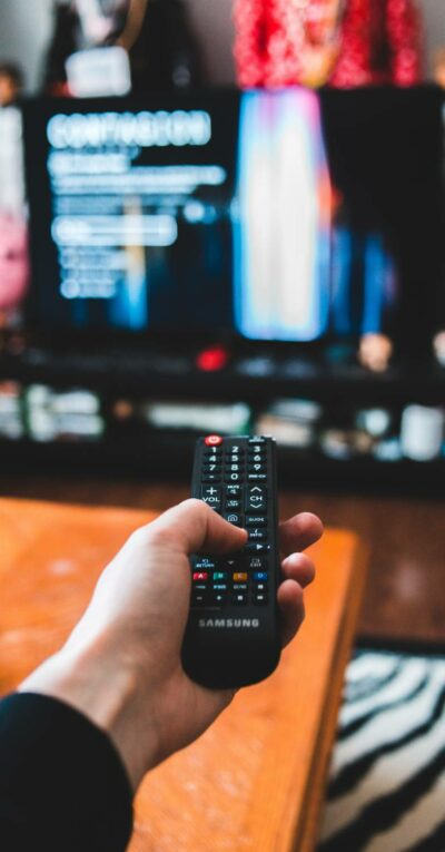 A man changes the TV channel with the remote