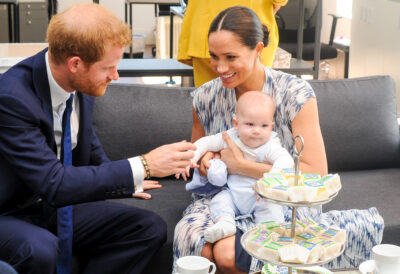 Meghan Markle and Prince Harry sat on a sofa with baby son Archie