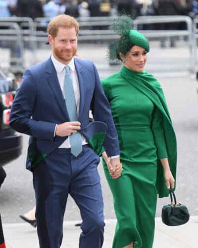 Prince harry dressed in a navy blue suit holds hands and smiles alongside wife meghan markle in a green dress and matching hat