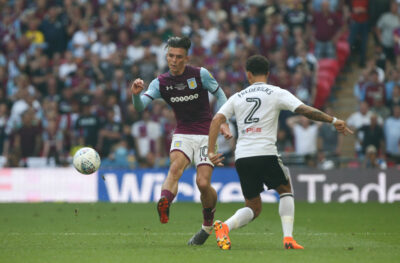 Jack Grealish passes the ball on pitch for Aston Villa against Fulham