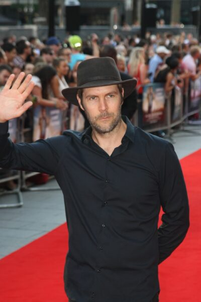 Rhod Gilbert waves to the camera and prepares for his new job on DIY SOS