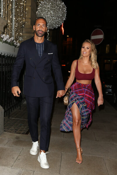 Rio Ferdinand in a black suit and grey t-short paired with white trainers and Kate Ferdinand wearing a burgundy crop top, heels and a check shirt around her waist holding hands