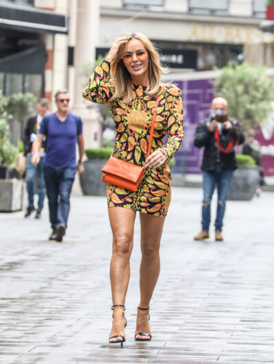 Amanda Holden smiles wearing yellow tinted sunglasses with a psychadelic print mini dress and strappy heels