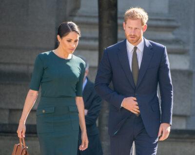 Meghan Markle walks beside Prince Harry. She wears a green midi dress with her hair tied back. He has on a navy blue suit.