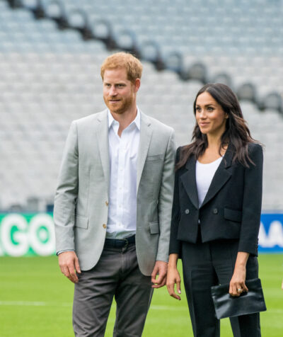 Prince Harry in a grey jacket and chinos with white shire stands beside meghan markle in a black trouser suit with white top