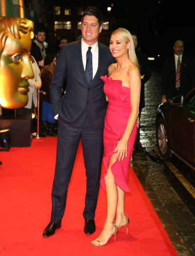 Tess Daly in a red evening gown with husband Vernon Kay in a dark blue suit on the red carpet