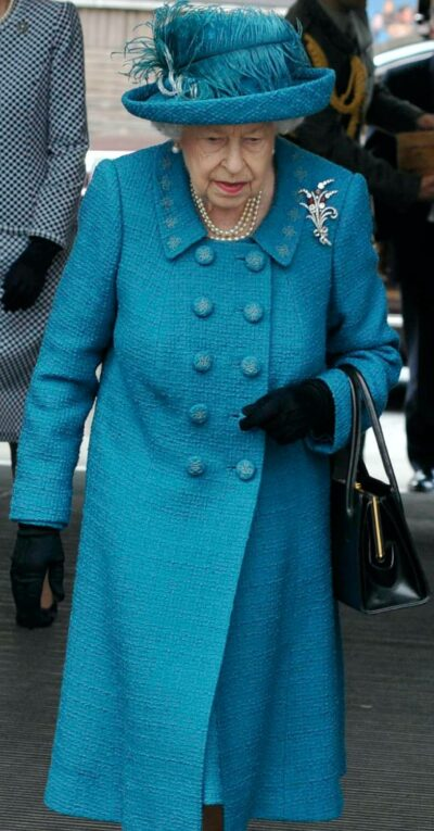 The Queen looks down as she walks through a Manchester train station