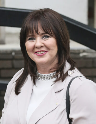 Coleen Nolan smiles at the camera wearing a pale pink blazer and cream high neck top with her hair down touching her shoulders