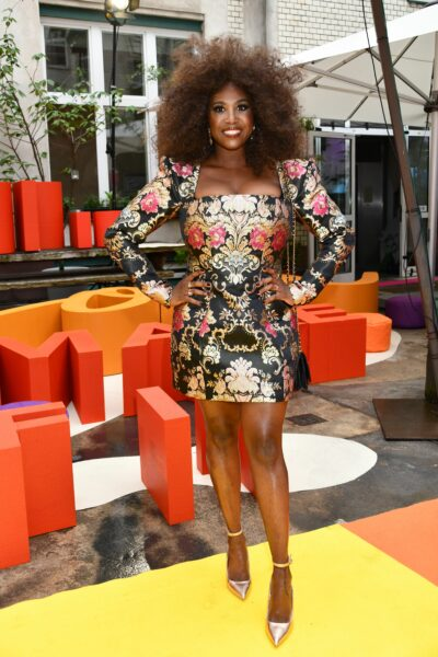 Motsi Mabuse posing in a printed mini dress with natural curls and a big smile