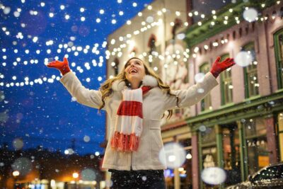A woman in a Christmas hat stood smiling in front of Christmas lights