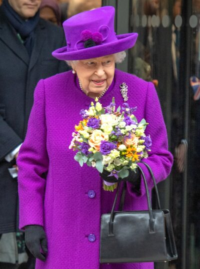 The Queen smiles and holds flowers during engagement