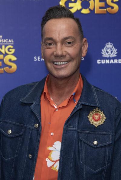 Craig Revel Horwood in an orange polo shirt and denim jacket smiling