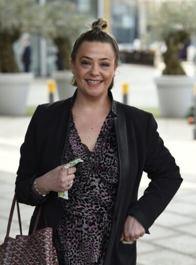 Lisa Armstrong smiling in black coat with hair up