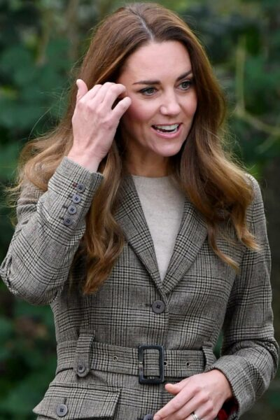 Kate Middleton sweeps her hair back with her hand