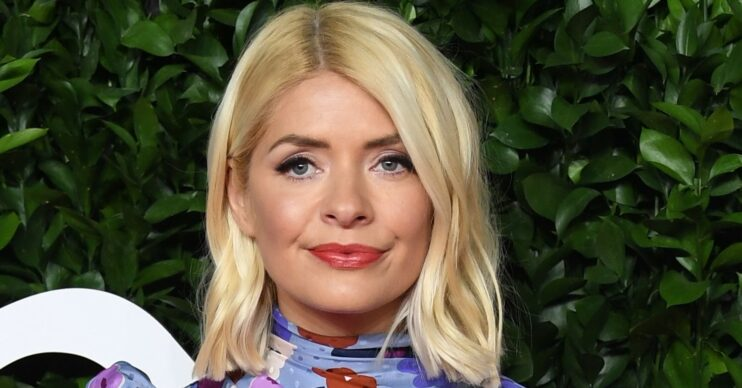 Holly Willoughby smiles on red carpet wearing a floral dress